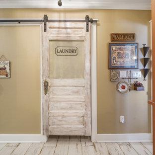 Inredning av en lantlig mycket stor tvättstuga, med beige väggar, mellanmörkt trägolv och brunt golv