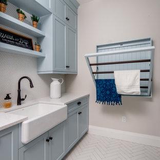 Esempio di una sala lavanderia country di medie dimensioni con lavello stile country, ante in stile shaker, ante blu, top in quarzo composito, paraspruzzi grigio, paraspruzzi con piastrelle in ceramica, pareti beige, lavatrice e asciugatrice a colonna, pavimento bianco e top bianco