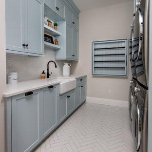 Idéer för mellanstora lantliga parallella vitt tvättstugor enbart för tvätt, med en rustik diskho, skåp i shakerstil, blå skåp, bänkskiva i kvarts, grått stänkskydd, stänkskydd i keramik, beige väggar, en tvättpelare och vitt golv