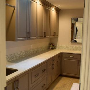 Foto på en mellanstor vintage vita parallell tvättstuga enbart för tvätt, med en undermonterad diskho, luckor med upphöjd panel, grå skåp, bänkskiva i kvarts, flerfärgad stänkskydd, stänkskydd i glaskakel, grå väggar, klinkergolv i porslin, en tvättmaskin och torktumlare bredvid varandra och grått golv
