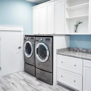 Esempio di una sala lavanderia contemporanea di medie dimensioni con ante in stile shaker, ante bianche, top in granito, pareti blu, pavimento in gres porcellanato, lavatrice e asciugatrice affiancate, pavimento grigio e top grigio