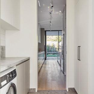 Idéer för en stor modern vita parallell tvättstuga enbart för tvätt, med en nedsänkt diskho, släta luckor, vita skåp, marmorbänkskiva, vitt stänkskydd, stänkskydd i keramik, vita väggar, klinkergolv i keramik, en tvättmaskin och torktumlare bredvid varandra och grått golv