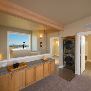 Idee per una piccola sala lavanderia classica con ante in stile shaker, ante in legno chiaro, top in granito, pareti beige, moquette, lavatrice e asciugatrice a colonna, pavimento grigio e top grigio
