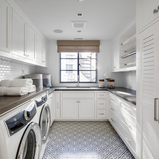 Ispirazione per una sala lavanderia costiera con ante in stile shaker, ante bianche, pareti bianche, lavatrice e asciugatrice affiancate, pavimento multicolore e top grigio