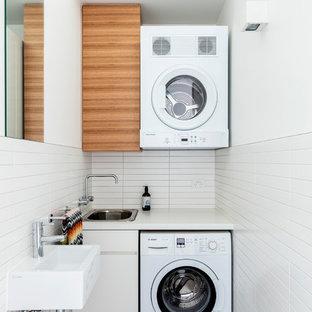Réalisation d'une buanderie linéaire design de taille moyenne avec un placard à porte plane, des portes de placard en bois brun, un mur blanc, des machines superposées, un sol noir et un plan de travail blanc.