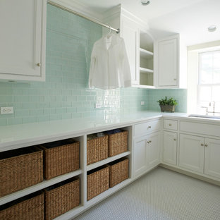 This is an example of a country separated utility room in New York with a submerged sink, white cabinets, composite countertops, green walls, ceramic flooring, a side by side washer and dryer, white floors, white worktops and beaded cabinets.