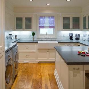 Bild på en mellanstor vintage u-formad tvättstuga enbart för tvätt, med en rustik diskho, luckor med glaspanel, vita skåp, bänkskiva i täljsten, vita väggar, mellanmörkt trägolv och en tvättmaskin och torktumlare bredvid varandra
