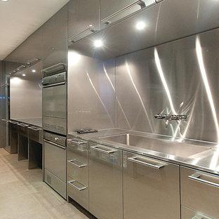 Esempio di un'ampia sala lavanderia con lavello integrato, ante lisce, ante in acciaio inossidabile e top in acciaio inossidabile