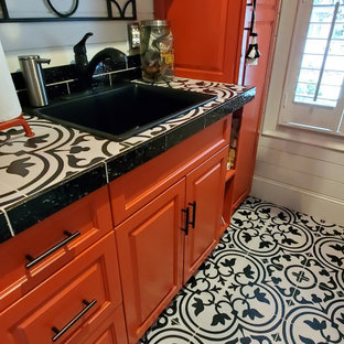 Ispirazione per una sala lavanderia bohémian di medie dimensioni con paraspruzzi nero, paraspruzzi con piastrelle in ceramica, pavimento in gres porcellanato, lavatrice e asciugatrice a colonna e pavimento nero