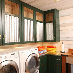 This is an example of a large country l-shaped dedicated laundry room in Other with green cabinets, white walls, a side-by-side washer and dryer, stainless steel benchtops and medium hardwood floors.