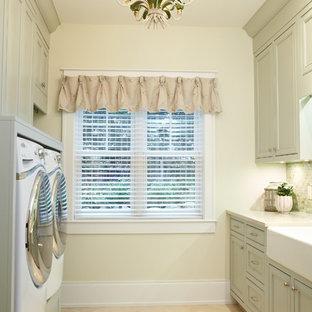 Imagen de lavadero clásico con fregadero sobremueble, puertas de armario verdes, paredes beige y suelo beige