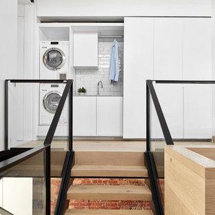 Exempel på en liten modern linjär liten tvättstuga, med släta luckor, vita skåp, bänkskiva i kvarts, vita väggar, ljust trägolv, en tvättpelare och beiget golv
