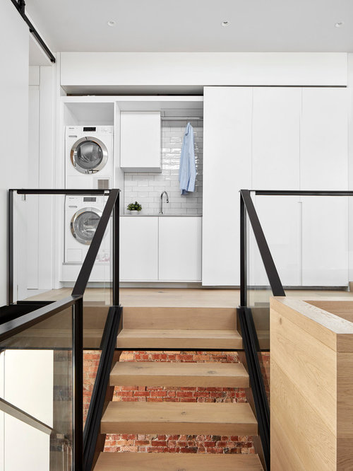 Small Contemporary Single Wall Light Wood Floor And Beige Laundry Closet Idea In Melbourne