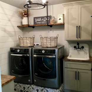 Example of a mid-sized cottage galley ceramic floor and black floor dedicated laundry room design in Other with shaker cabinets, beige cabinets, wood countertops, gray walls, a side-by-side washer/dryer and a drop-in sink