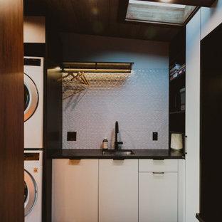 Idéer för en liten modern svarta linjär tvättstuga enbart för tvätt, med en enkel diskho, släta luckor, vita skåp, vitt stänkskydd, stänkskydd i mosaik, vita väggar, en tvättpelare och beiget golv