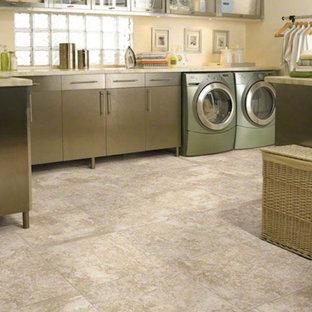 Idéer för stora l-formade tvättstugor enbart för tvätt, med luckor med glaspanel, skåp i rostfritt stål, granitbänkskiva, beige väggar, kalkstensgolv och en tvättmaskin och torktumlare bredvid varandra