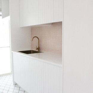 Пример оригинального дизайна: отдельная, прямая прачечная среднего размера в стиле модернизм с накладной раковиной, фасадами в стиле шейкер, белыми фасадами, столешницей из кварцевого агломерата, розовым фартуком, фартуком из плитки мозаики, белыми стенами, полом из керамогранита, с сушильной машиной на стиральной машине, белым полом и белой столешницей