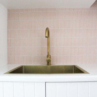 На фото: отдельная, прямая прачечная среднего размера в стиле модернизм с накладной раковиной, фасадами в стиле шейкер, белыми фасадами, столешницей из кварцевого агломерата, розовым фартуком, фартуком из плитки мозаики, белыми стенами, полом из керамогранита, с сушильной машиной на стиральной машине, белым полом и белой столешницей