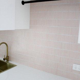 Idéer för en mellanstor modern vita linjär tvättstuga enbart för tvätt, med en nedsänkt diskho, skåp i shakerstil, vita skåp, bänkskiva i kvarts, rosa stänkskydd, stänkskydd i mosaik, vita väggar, klinkergolv i porslin, en tvättpelare och vitt golv
