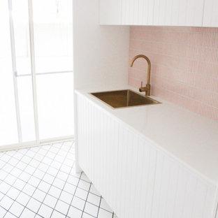 Inredning av en modern mellanstor vita linjär vitt tvättstuga enbart för tvätt, med en nedsänkt diskho, skåp i shakerstil, vita skåp, bänkskiva i kvarts, rosa stänkskydd, stänkskydd i mosaik, vita väggar, klinkergolv i porslin, en tvättpelare och vitt golv
