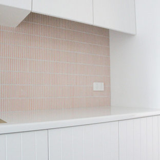 Стильный дизайн: отдельная, прямая прачечная среднего размера в стиле модернизм с накладной раковиной, фасадами в стиле шейкер, белыми фасадами, столешницей из кварцевого агломерата, розовым фартуком, фартуком из плитки мозаики, белыми стенами, полом из керамогранита, с сушильной машиной на стиральной машине, белым полом и белой столешницей - последний тренд