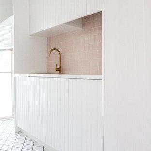 Exempel på en mellanstor modern vita linjär vitt tvättstuga enbart för tvätt, med en nedsänkt diskho, skåp i shakerstil, vita skåp, bänkskiva i kvarts, rosa stänkskydd, stänkskydd i mosaik, vita väggar, klinkergolv i porslin, en tvättpelare och vitt golv