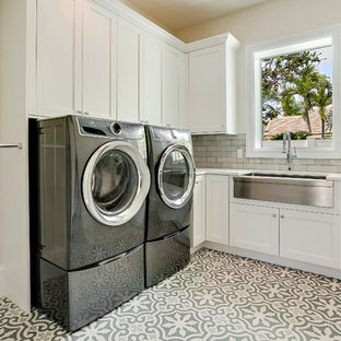 This is an example of a large mediterranean l-shaped separated utility room in Miami with a belfast sink, white cabinets, engineered stone countertops, beige walls, porcelain flooring, a side by side washer and dryer, multi-coloured floors, white worktops and shaker cabinets.