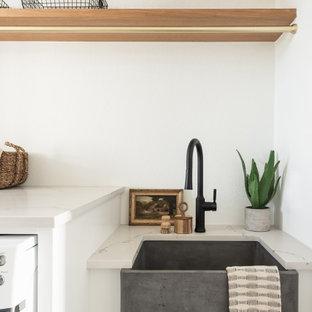 Cette photo montre une grand buanderie parallèle moderne dédiée avec un évier de ferme, des portes de placard blanches, un mur blanc, un sol en bois clair et un plan de travail beige.