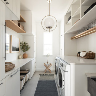 This is an example of a large transitional galley dedicated laundry room in Dallas with a farmhouse sink, white cabinets, white walls, beige benchtop, flat-panel cabinets, a side-by-side washer and dryer and grey floor.