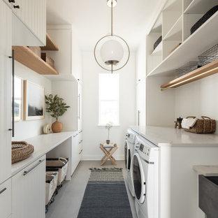 ダラスの広いトランジショナルスタイルのおしゃれな洗濯室 (ll型、エプロンフロントシンク、白いキャビネット、白い壁、ベージュのキッチンカウンター、フラットパネル扉のキャビネット、左右配置の洗濯機・乾燥機、グレーの床) の写真