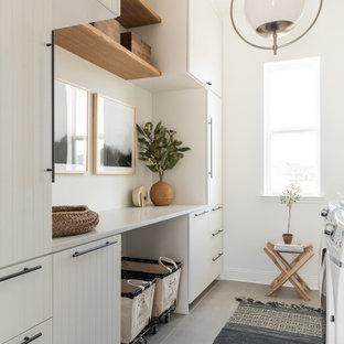 Inredning av en modern stor beige parallell beige tvättstuga enbart för tvätt, med en rustik diskho, vita skåp, vita väggar och ljust trägolv