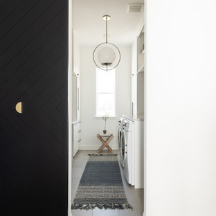 Photo of a large modern galley dedicated laundry room in Dallas with a farmhouse sink, white cabinets, white walls, light hardwood floors and beige benchtop.