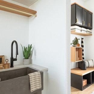 Réalisation d'une grand buanderie parallèle minimaliste dédiée avec un évier de ferme, des portes de placard blanches, un mur blanc, un sol en bois clair et un plan de travail beige.