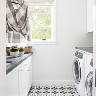 Idéer för att renovera en mellanstor maritim grå parallell grått tvättstuga enbart för tvätt, med en undermonterad diskho, skåp i shakerstil, vita skåp, vita väggar, en tvättmaskin och torktumlare bredvid varandra och grått golv