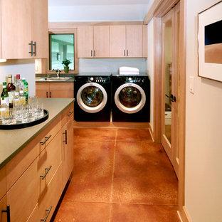 Ispirazione per una lavanderia contemporanea con pavimento in cemento e pavimento arancione