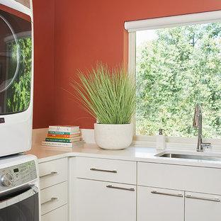 Exempel på en stor modern vita l-formad vitt tvättstuga enbart för tvätt, med en undermonterad diskho, släta luckor, vita skåp, bänkskiva i kvarts, röda väggar, klinkergolv i keramik, en tvättpelare och brunt golv