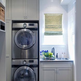 Klassisk inredning av ett litet linjärt grovkök, med en nedsänkt diskho, skåp i shakerstil, grå skåp, laminatbänkskiva, vita väggar, klinkergolv i keramik och en tvättpelare