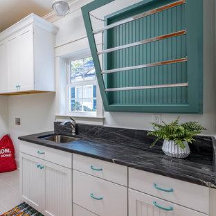 Inspiration för mellanstora klassiska linjära svart grovkök, med en undermonterad diskho, luckor med infälld panel, vita skåp, granitbänkskiva, vita väggar, klinkergolv i keramik och en tvättmaskin och torktumlare bredvid varandra