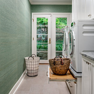 Inspiration for a transitional single-wall dedicated laundry room in Nashville with shaker cabinets, white cabinets, green walls, a side-by-side washer and dryer, beige floor and wallpaper.