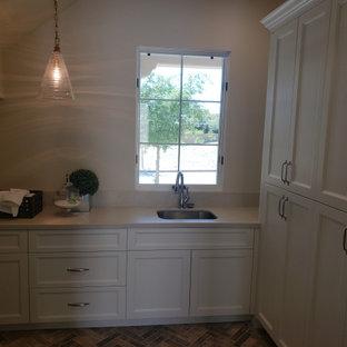 Idéer för att renovera en mellanstor medelhavsstil grå grått tvättstuga enbart för tvätt, med en undermonterad diskho, luckor med upphöjd panel, vita skåp, granitbänkskiva, grått stänkskydd, beige väggar, tegelgolv och brunt golv