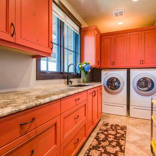 Idéer för en stor amerikansk flerfärgade l-formad tvättstuga enbart för tvätt, med en undermonterad diskho, luckor med profilerade fronter, orange skåp, granitbänkskiva, beige väggar, klinkergolv i keramik, en tvättmaskin och torktumlare bredvid varandra och beiget golv