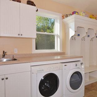 Ispirazione per una lavanderia multiuso stile americano di medie dimensioni con ante bianche, top in laminato, pavimento con piastrelle in ceramica, lavatrice e asciugatrice affiancate, lavello da incasso, ante lisce e pareti arancioni