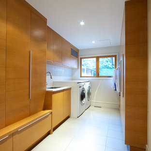 Large trendy galley porcelain floor and white floor dedicated laundry room photo in Vancouver with an undermount sink, flat-panel cabinets, medium tone wood cabinets, white walls, a side-by-side washer/dryer and quartz countertops