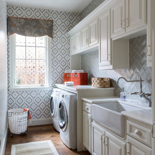 Elegant single-wall medium tone wood floor and brown floor dedicated laundry room photo in Dallas with a farmhouse sink, raised-panel cabinets, white cabinets, multicolored walls, a side-by-side washer/dryer and white countertops