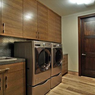 Idéer för funkis tvättstugor, med en nedsänkt diskho, släta luckor, skåp i mörkt trä, en tvättmaskin och torktumlare bredvid varandra och brunt golv