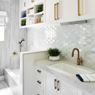 Inredning av en klassisk mellanstor grå parallell grått tvättstuga enbart för tvätt, med en undermonterad diskho, skåp i shakerstil, vita skåp, bänkskiva i kvarts, blå väggar, klinkergolv i porslin, en tvättmaskin och torktumlare bredvid varandra och grått golv