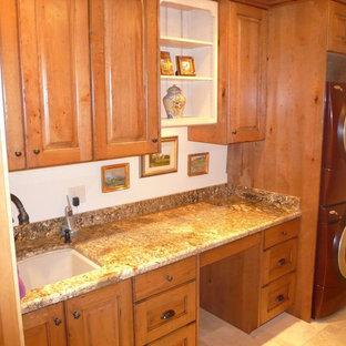 Ispirazione per una sala lavanderia american style di medie dimensioni con lavello sottopiano, ante in stile shaker, ante in legno chiaro, top in granito, pareti bianche, pavimento in ardesia, lavatrice e asciugatrice a colonna, pavimento beige e top marrone
