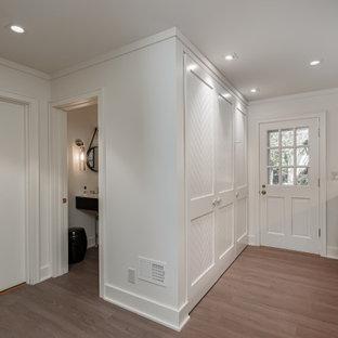 Exempel på ett stort modernt grå l-format grått grovkök, med en undermonterad diskho, luckor med lamellpanel, bruna skåp, bänkskiva i kvarts, grått stänkskydd, gula väggar, vinylgolv, en tvättmaskin och torktumlare bredvid varandra och grått golv