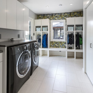 Inspiration for a large contemporary single-wall utility room in Milwaukee with flat-panel cabinets, white cabinets, quartz worktops, grey walls, laminate floors, a side by side washer and dryer, white floors and grey worktops.