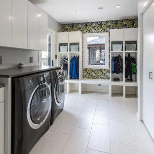 Immagine di una grande lavanderia multiuso design con ante lisce, ante bianche, top in quarzite, pareti grigie, pavimento in laminato, lavatrice e asciugatrice affiancate, pavimento bianco e top grigio